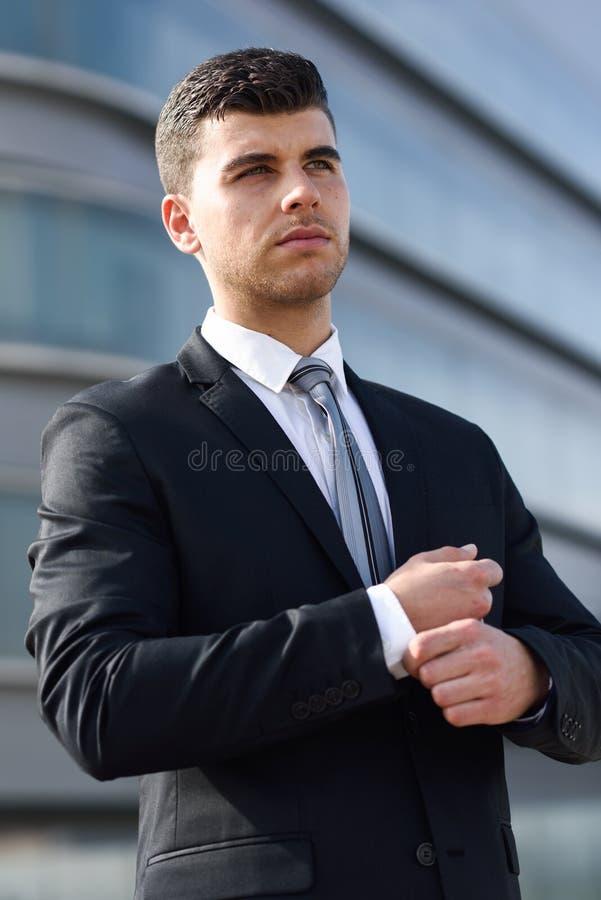 Jonge zakenman dichtbij een bureaugebouw die zwart kostuum dragen royalty-vrije stock afbeelding