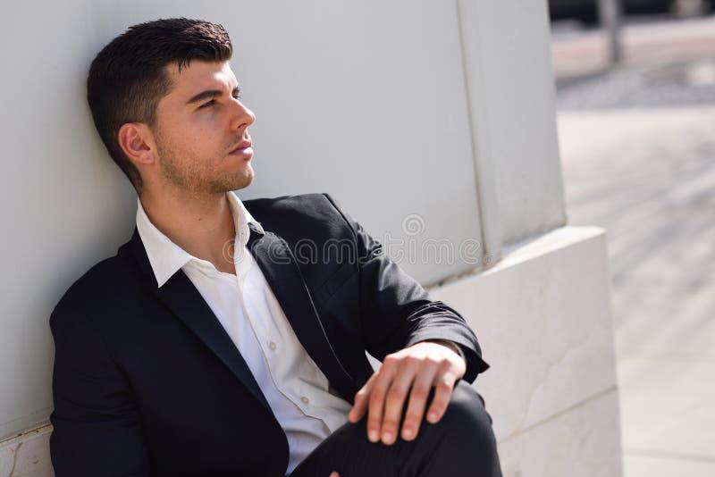Jonge zakenman dichtbij een bureaugebouw die zwart kostuum dragen royalty-vrije stock fotografie