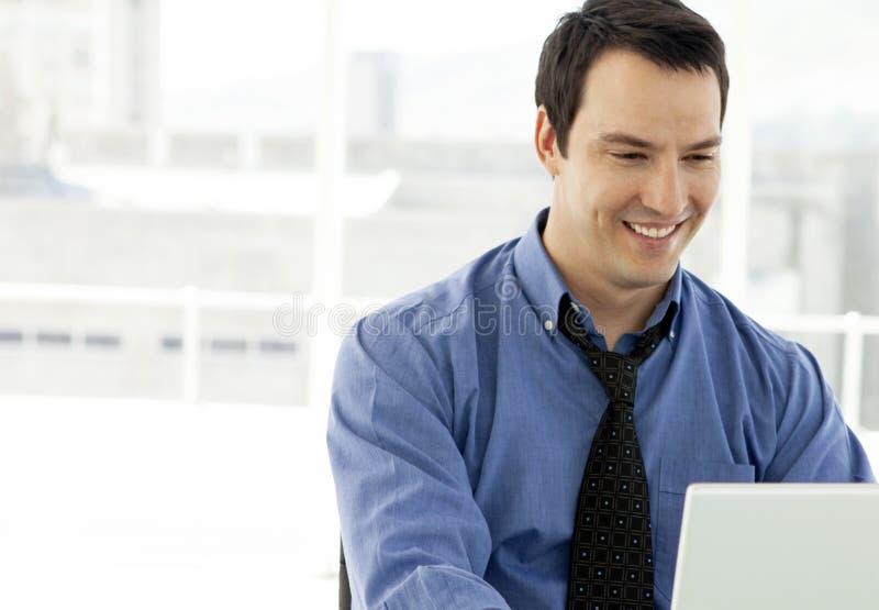 Jonge zakenman die aan laptop in bureau werken stock foto's