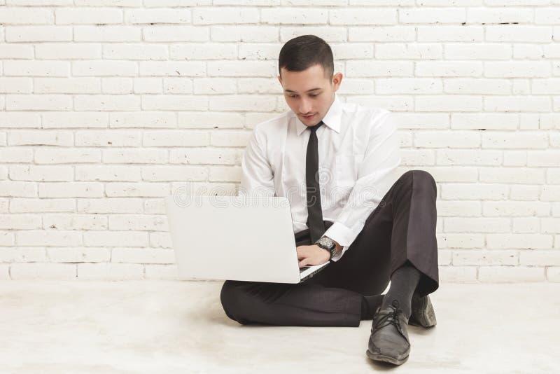 Jonge zakenman die aan laptop werken terwijl het zitten op de vloer royalty-vrije stock fotografie