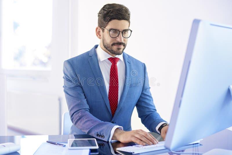 Jonge zakenman die aan zijn computer werken terwijl het zitten bij offic royalty-vrije stock afbeeldingen