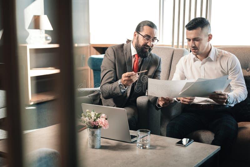 Jonge zakenman die aan zijn gebaarde investeerder spreken die glazen dragen royalty-vrije stock foto