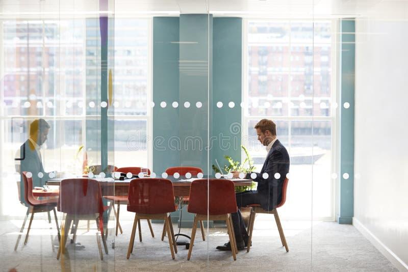 Jonge zakenman die alleen in een bureauvergaderzaal werken royalty-vrije stock afbeelding