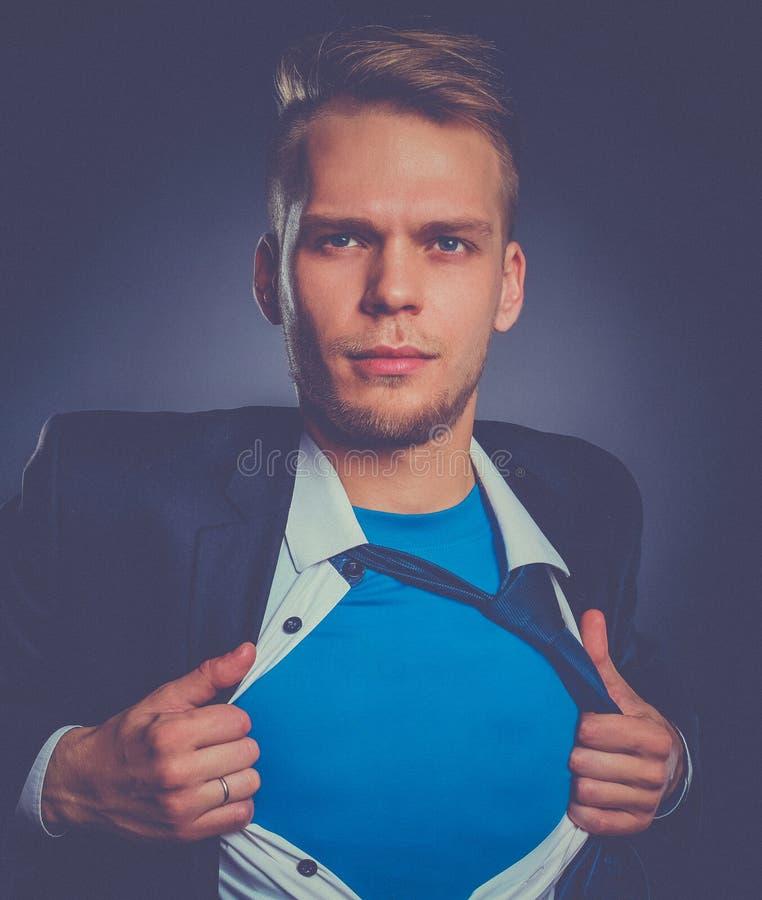 Jonge zakenman die als een super held handelen en tearing zijn geïsoleerd overhemd, op grijze achtergrond stock afbeelding
