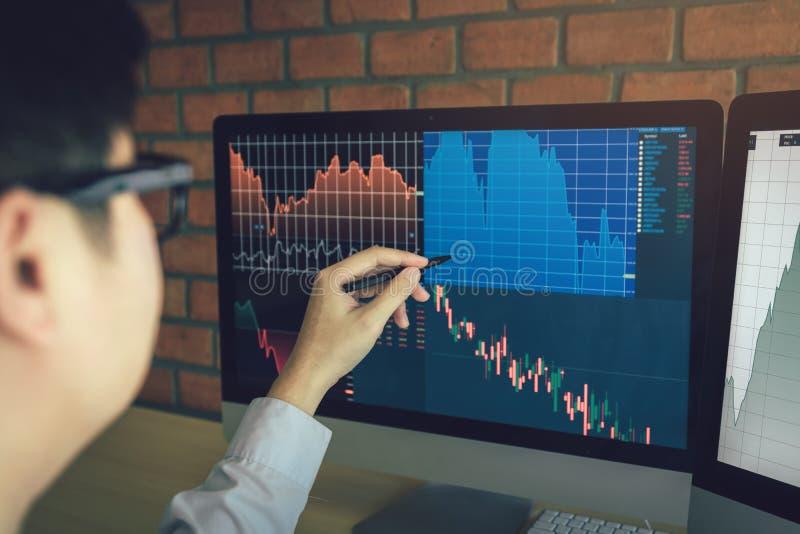Jonge zakenman die bij effectenbeurs met het computerscherm bij bureau werken royalty-vrije stock fotografie