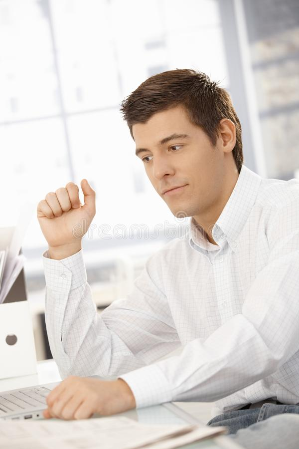 Jonge zakenman die in bureau denkt royalty-vrije stock foto's