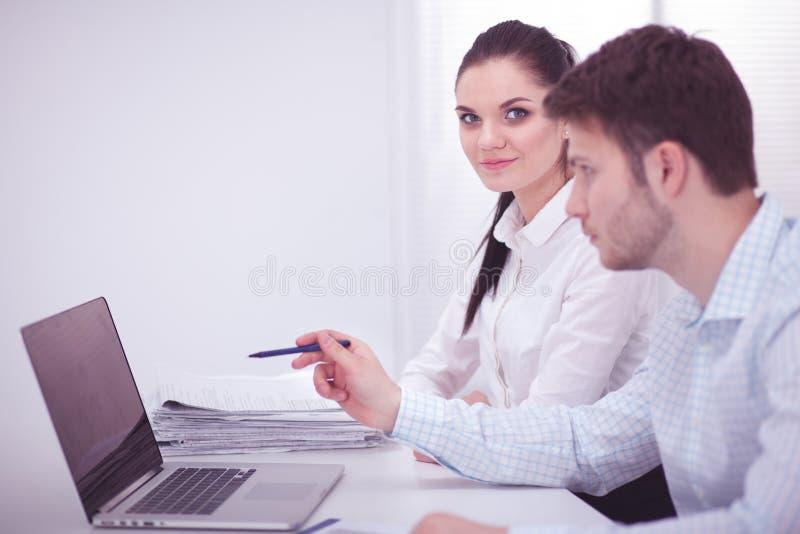 Jonge zakenman die in bureau werken, zittend bij bureau, die laptop het computerscherm bekijken royalty-vrije stock fotografie