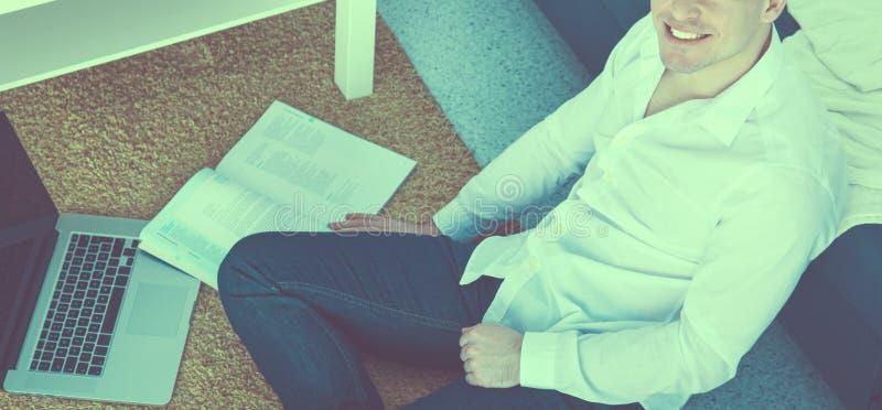 Jonge zakenman die in bureau werkt, dat bij bureau zit royalty-vrije stock afbeelding