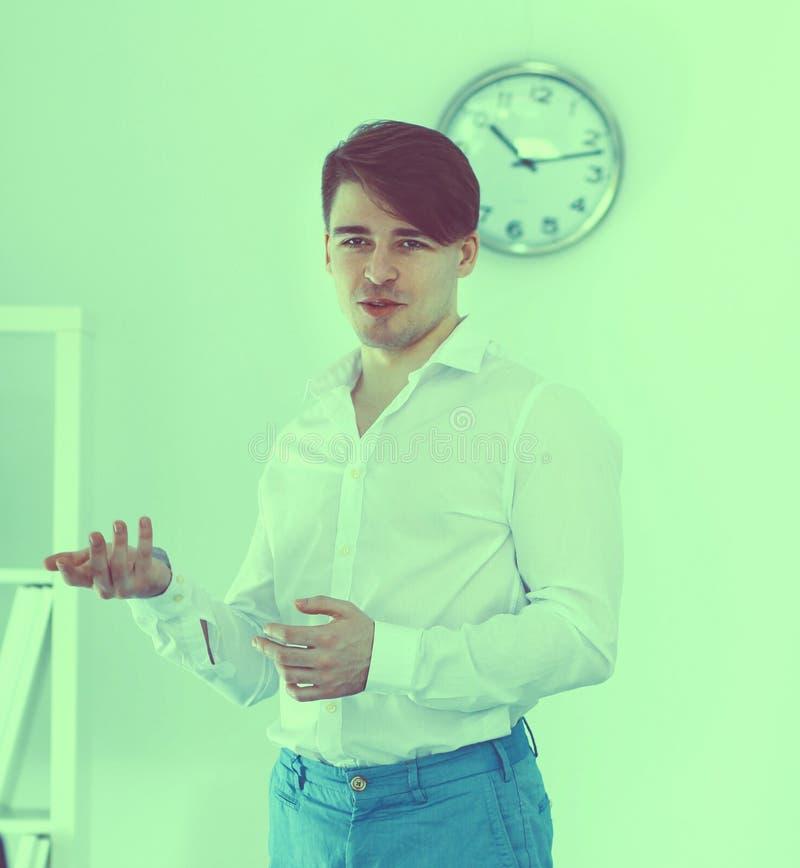 Jonge zakenman die in bureau werkt, dat bij bureau zit stock foto