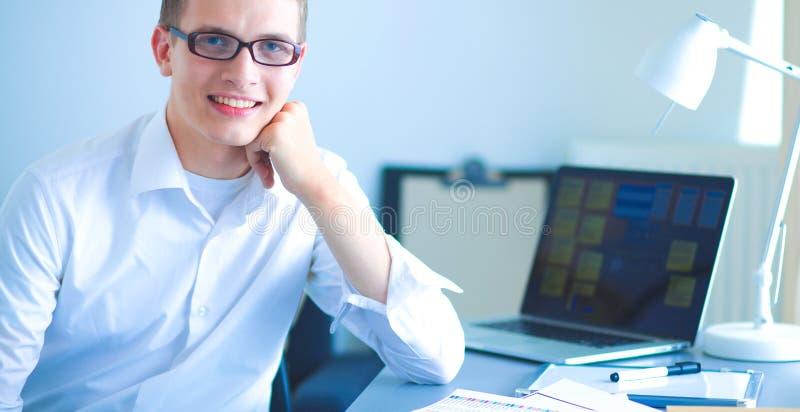 Jonge zakenman die in bureau werkt, dat dichtbij bureau zit stock afbeeldingen