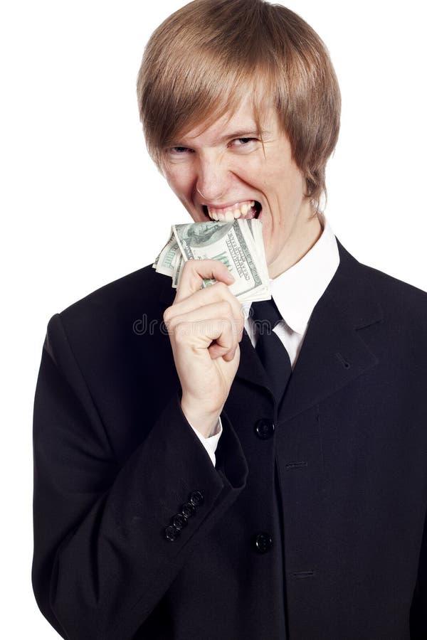 Jonge zakenman die contant geld eet stock foto