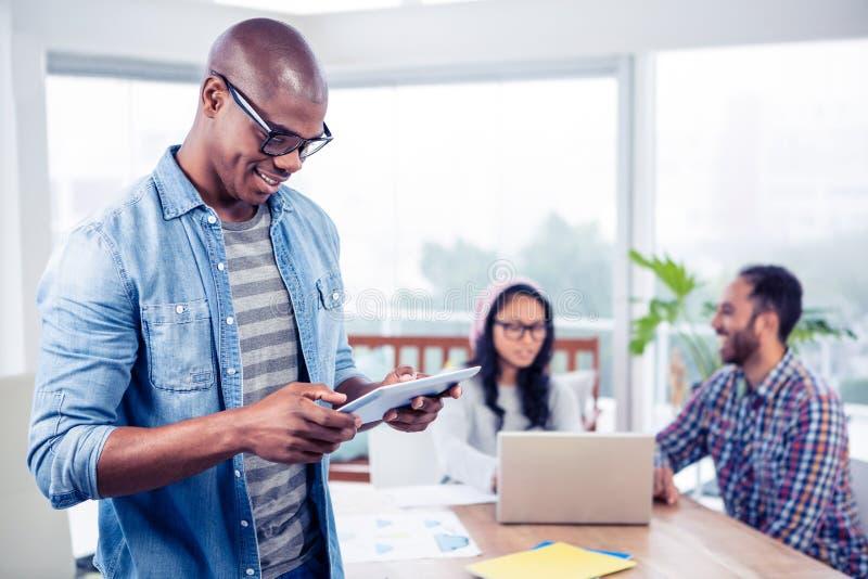Jonge zakenman die digitale tablet gebruiken terwijl status in bureau stock afbeelding