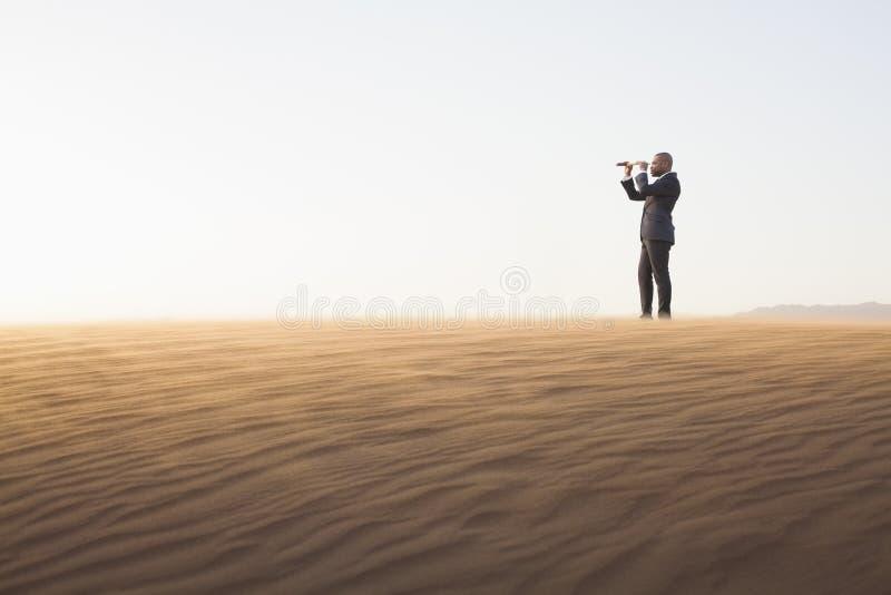 Jonge zakenman die door telescoop in het midden van de woestijn kijken royalty-vrije stock fotografie