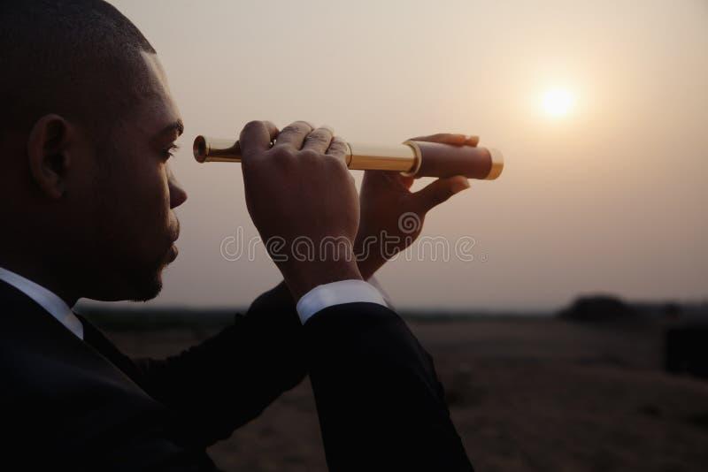 Jonge zakenman die door telescoop in het midden van de woestijn kijken stock foto's