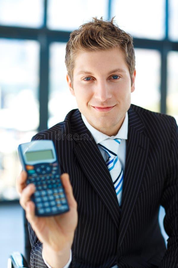 Jonge zakenman die een calculator houdt royalty-vrije stock afbeelding