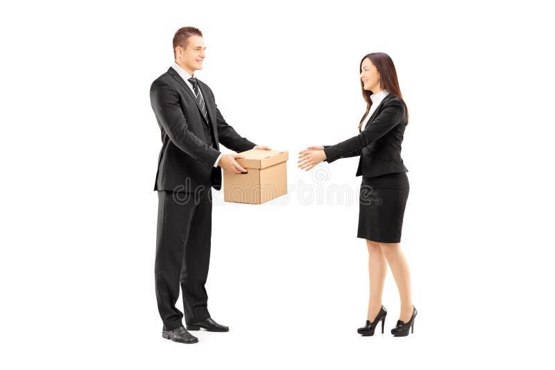 Jonge zakenman die een doos geeft aan zijn vrouwelijke collega stock afbeelding