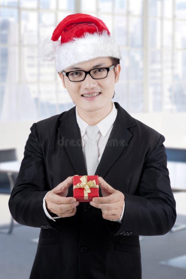 Jonge zakenman die een Kerstmisgift tonen royalty-vrije stock fotografie