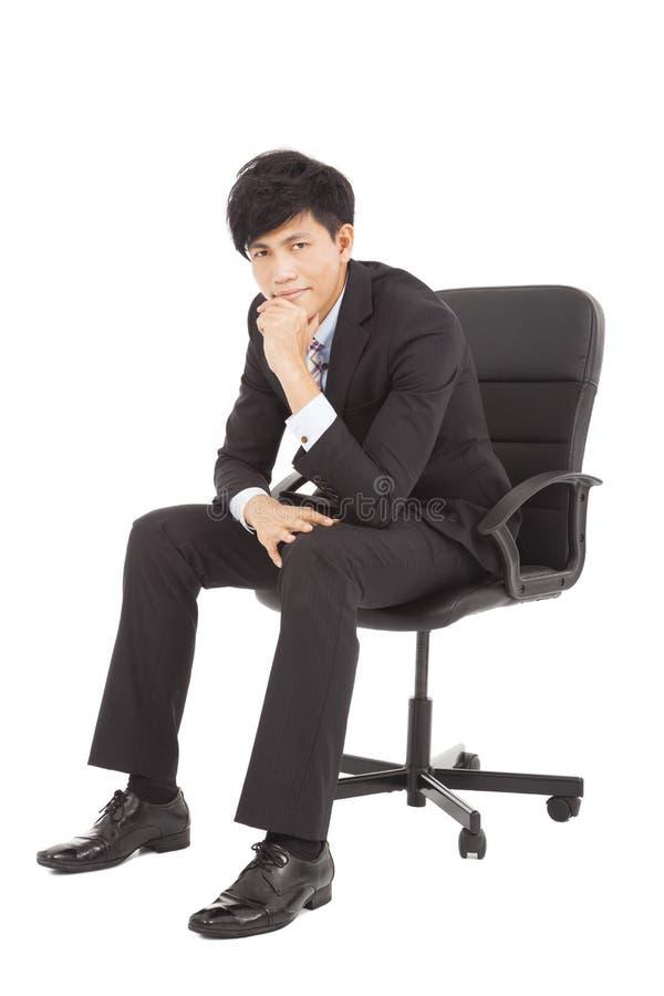 Jonge zakenman die en als voorzitter denkt zit stock foto