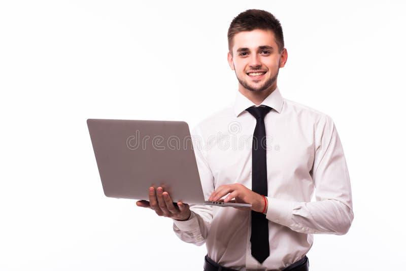 Jonge zakenman die en laptop over witte achtergrond bevinden zich met behulp van stock fotografie