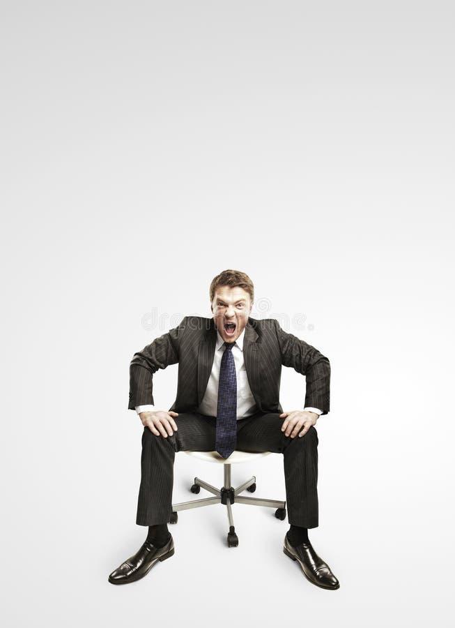 Jonge zakenman die en op een stoel schreeuwt zit. stock fotografie