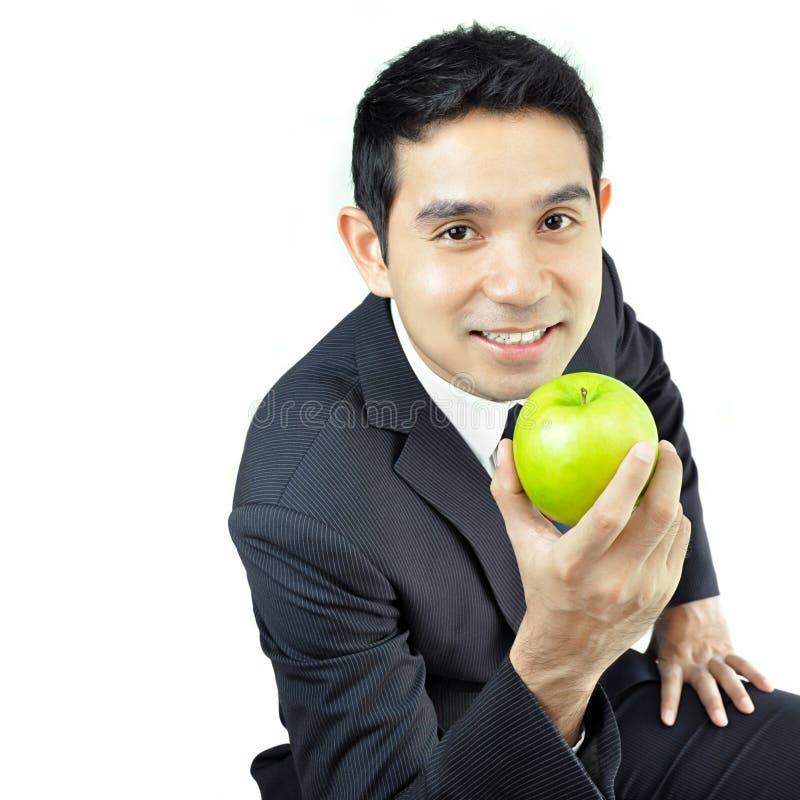 Jonge zakenman die groene appel met het glimlachen gezicht houden stock foto's