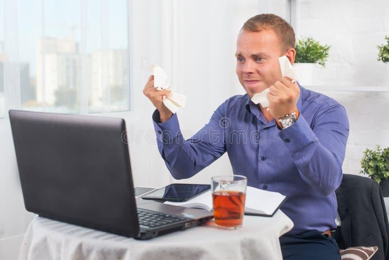 Jonge zakenman die in het zeer betrokken bureau werken, een paniek, verfrommeld document royalty-vrije stock foto