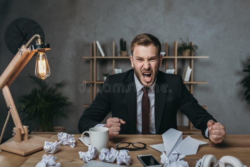 Jonge zakenman die in kostuum terwijl het zitten op het slordige werk schreeuwen stock afbeelding