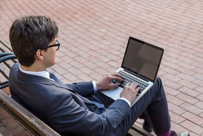 Jonge zakenman die laptop kant gebruiken royalty-vrije stock foto's