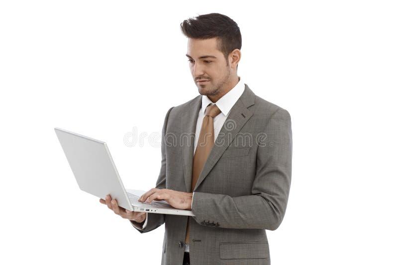 Jonge zakenman die laptop met behulp van royalty-vrije stock afbeeldingen