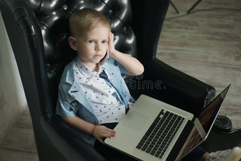 Jonge zakenman die laptop met behulp van Grappig kind in glazen Manierportret van weinig knappe jongen in bureau royalty-vrije stock foto's