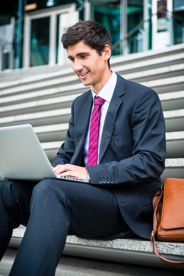 Jonge zakenman die laptop met behulp van terwijl in openlucht het gaan zitten royalty-vrije stock foto's
