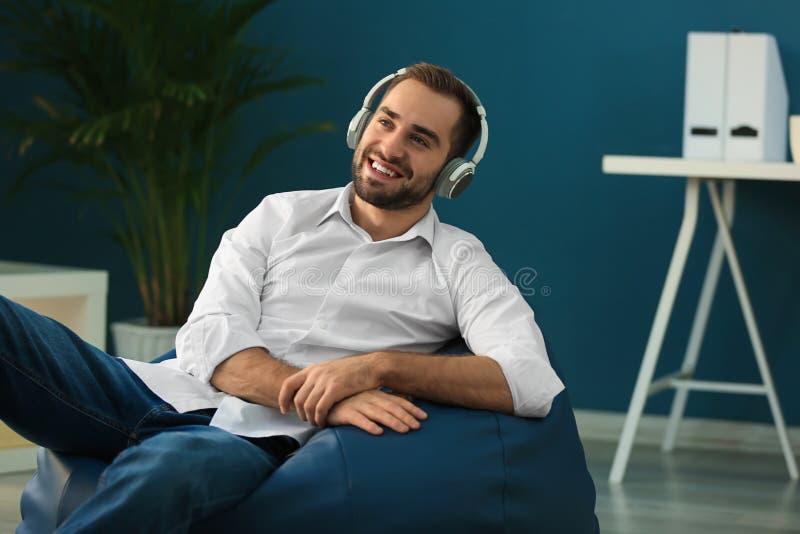 Jonge zakenman die met hoofdtelefoons op beanbagstoel zitten in bureau royalty-vrije stock fotografie
