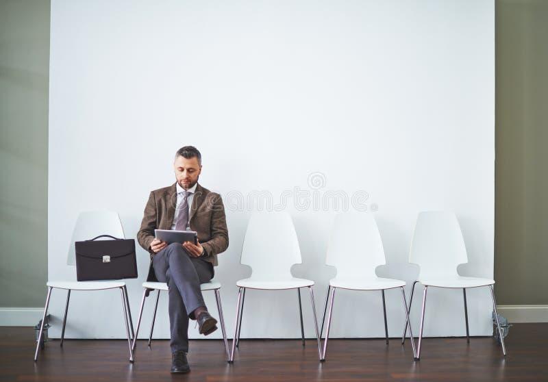 Jonge zakenman die met krant wacht royalty-vrije stock afbeeldingen