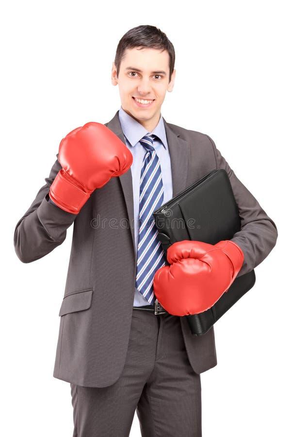 Jonge zakenman die met rode bokshandschoenen een aktentas houdt stock afbeelding