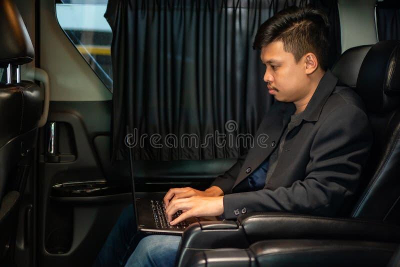 Jonge zakenman die mobiele telefoon en laptop in auto met behulp van royalty-vrije stock foto's