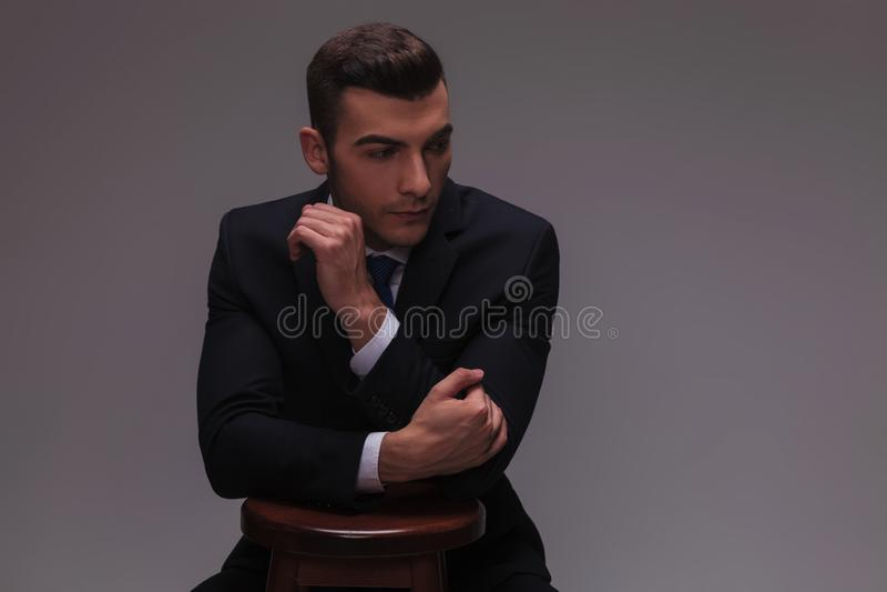 Jonge zakenman die modieus met handen op een stoel zijn stock fotografie