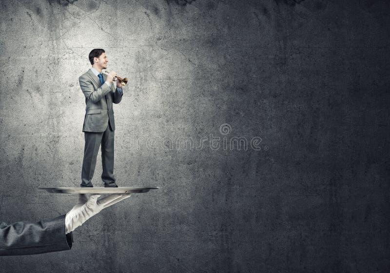 Jonge zakenman die op metaaldienblad Fife spelen tegen concrete achtergrond royalty-vrije stock fotografie