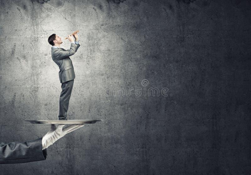 Jonge zakenman die op metaaldienblad Fife spelen tegen concrete achtergrond royalty-vrije stock afbeeldingen