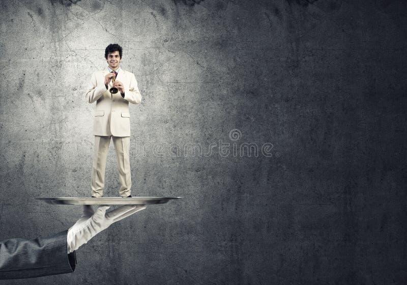 Jonge zakenman die op metaaldienblad Fife spelen tegen concrete achtergrond royalty-vrije stock foto's