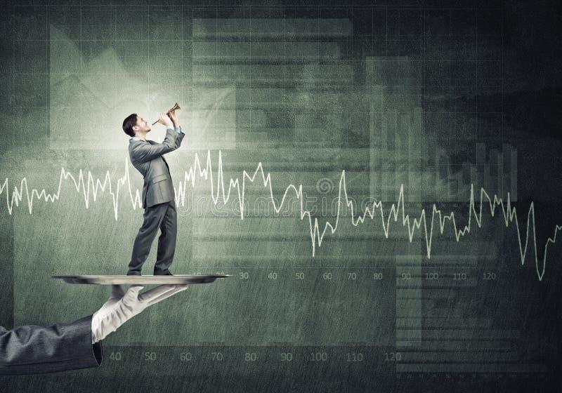 Jonge zakenman die op metaaldienblad Fife spelen tegen concrete achtergrond met grafiek royalty-vrije stock foto's
