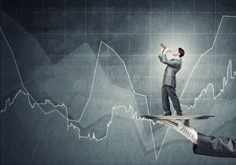 Jonge zakenman die op metaaldienblad Fife spelen tegen concrete achtergrond met grafiek stock afbeelding