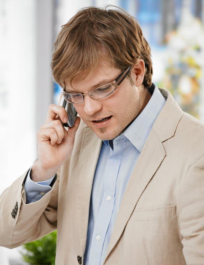 Jonge zakenman die op mobiele telefoon spreekt stock fotografie