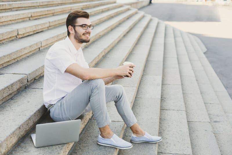 Jonge zakenman die rust met koffie hebben in openlucht stock fotografie