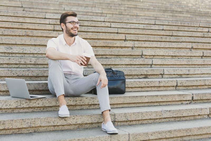Jonge zakenman die rust met koffie hebben in openlucht stock afbeeldingen
