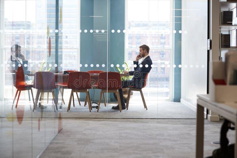 Jonge zakenman die telefoon in een bureauvergaderzaal met behulp van stock afbeeldingen