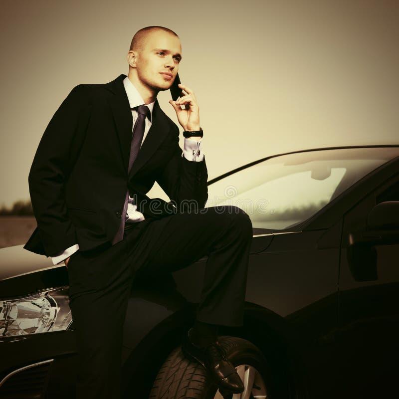 Jonge zakenman die telefoonzitting op zijn auto uitnodigen stock foto's