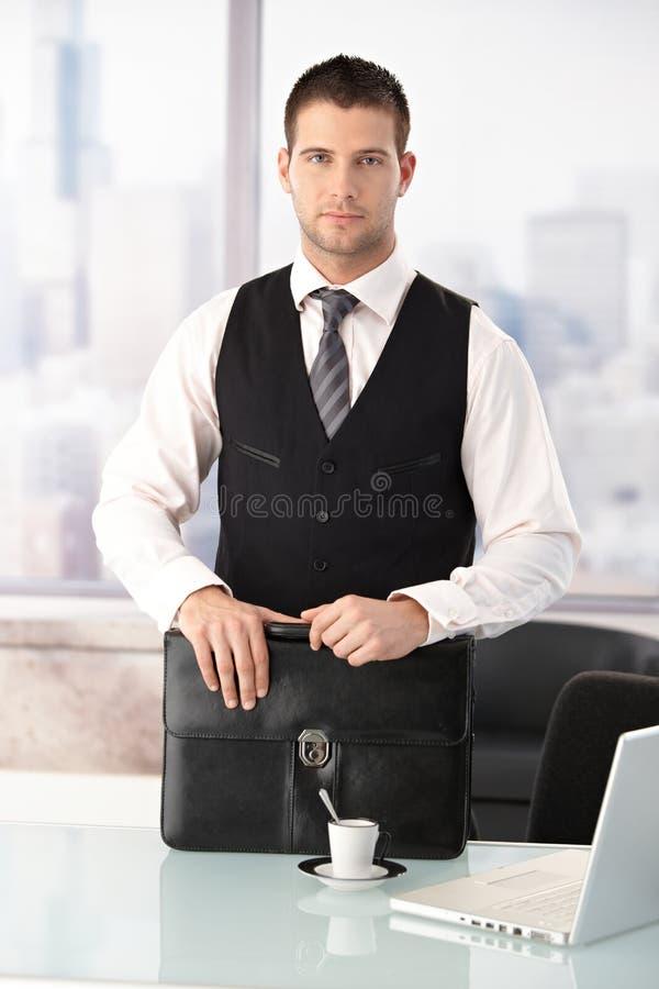 Jonge zakenman die zich bij bureau in bureau bevindt royalty-vrije stock fotografie