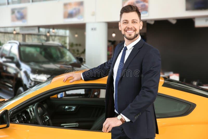 Jonge zakenman die zich dichtbij auto in salon bevinden royalty-vrije stock fotografie