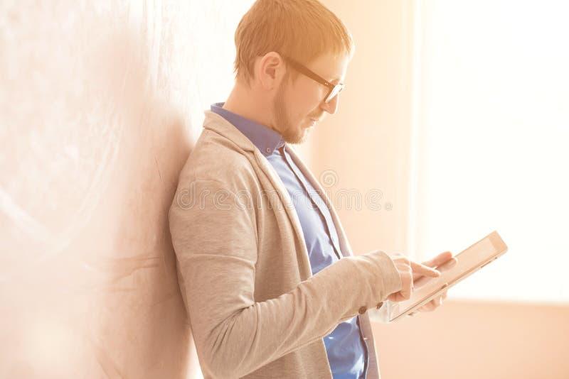 Jonge zakenman die zich in een bureau dichtbij het venster en de muur bevinden en tabletpc met behulp van stock afbeelding