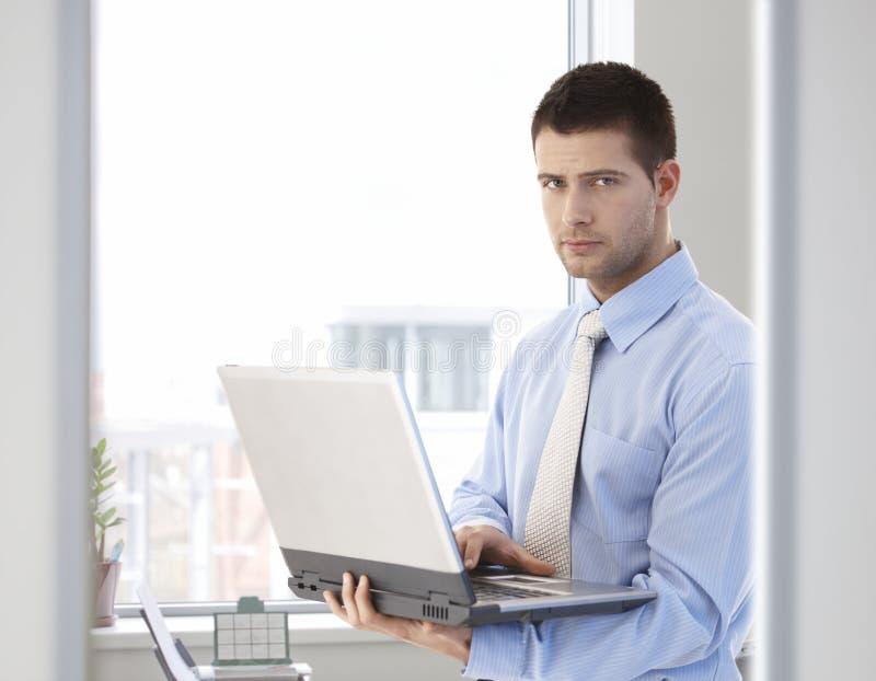 Jonge zakenman die zich met in hand laptop bevindt royalty-vrije stock foto's